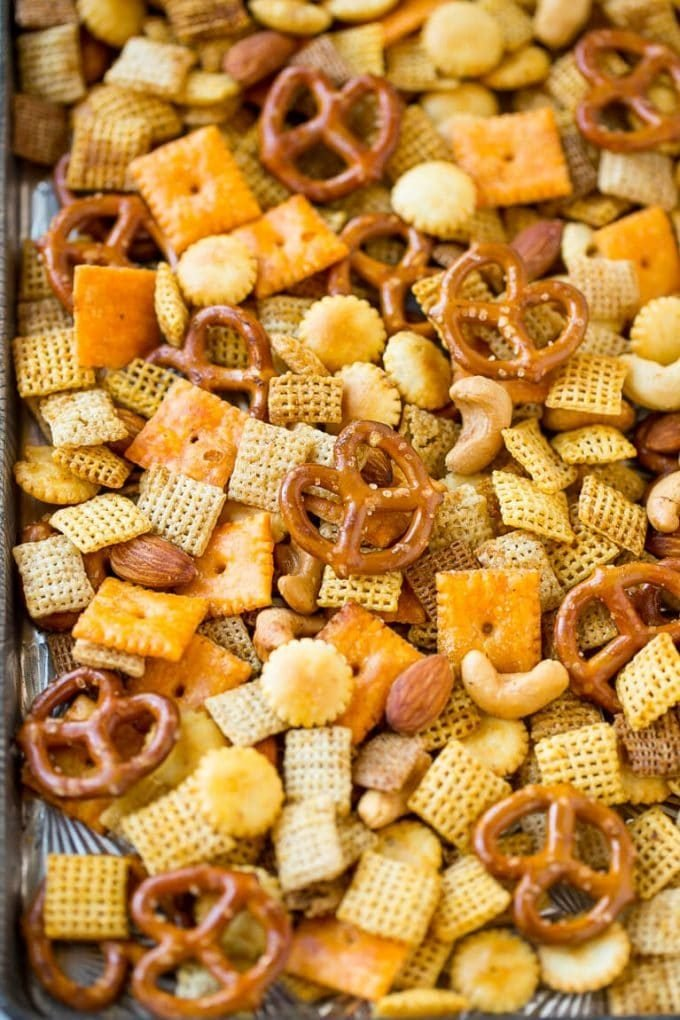 A sheet pan full of homemade chex mix made with cereal, crackers, pretzels and nuts.