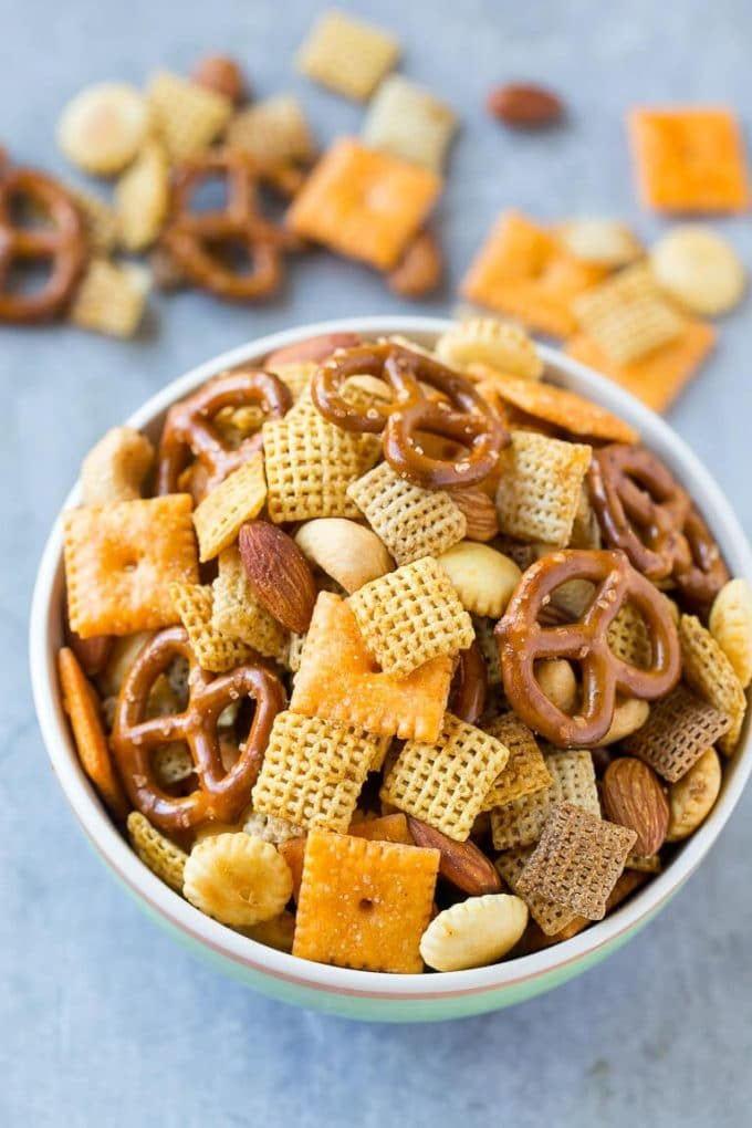 A bowl full of chex party mix made with crackers, cereal and almonds.