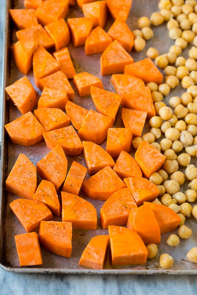 Raw sweet potatoes and canned chickpeas on a sheet pan.