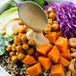 Buddha Bowl with quinoa, chickpeas, sweet potatoes, avocado, cabbage, tahini dressing poured over the top
