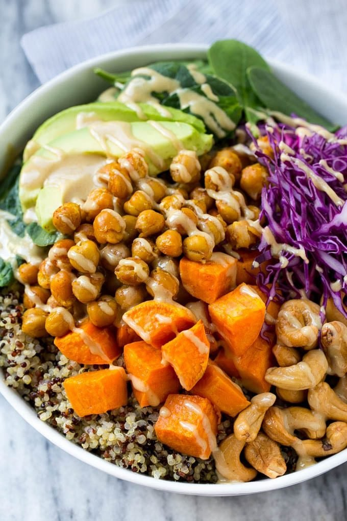 A Buddha bowl filled with quinoa, sweet potatoes, chickpeas and avocado, then drizzled with tahini dressing.