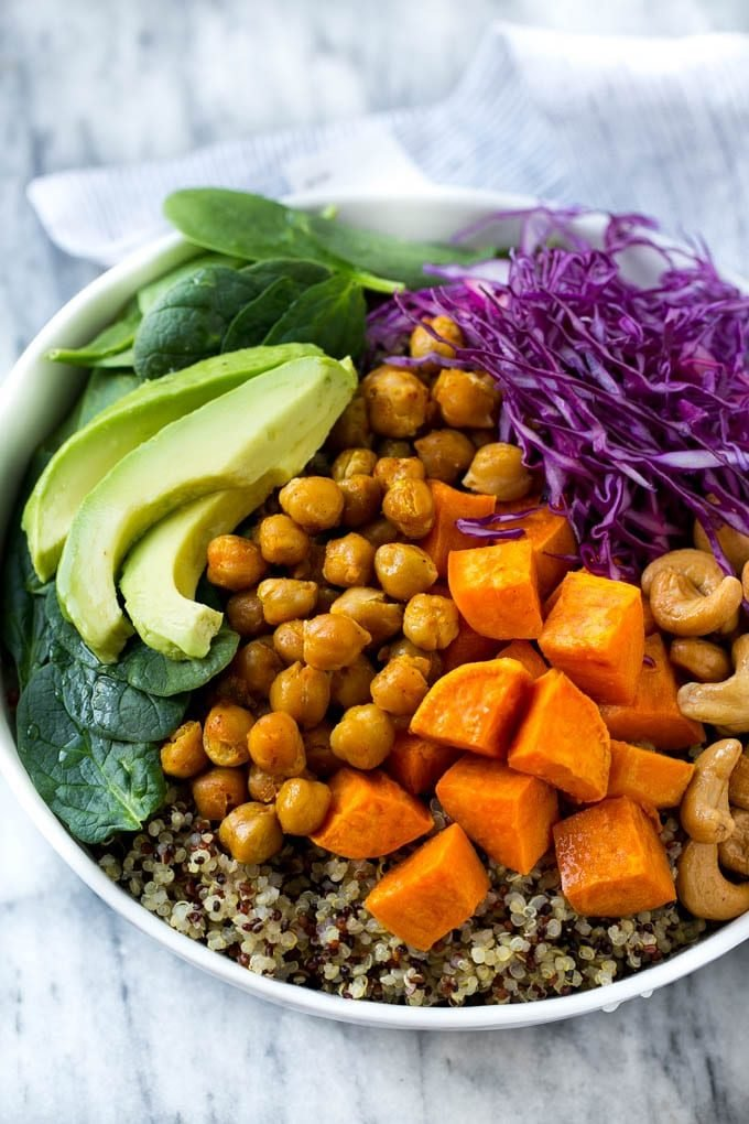 Sweet potatoes, chickpeas, avocado and quinoa arranged over purple cabbage in a bowl.