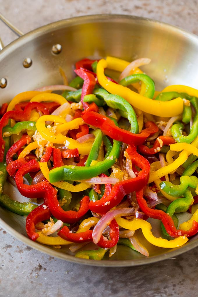 Sauteed bell peppers and onions in a pan.