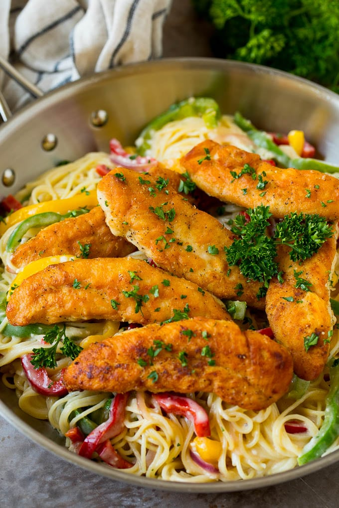 Chicken scampi with breaded chicken tenders served over creamy pasta and peppers.