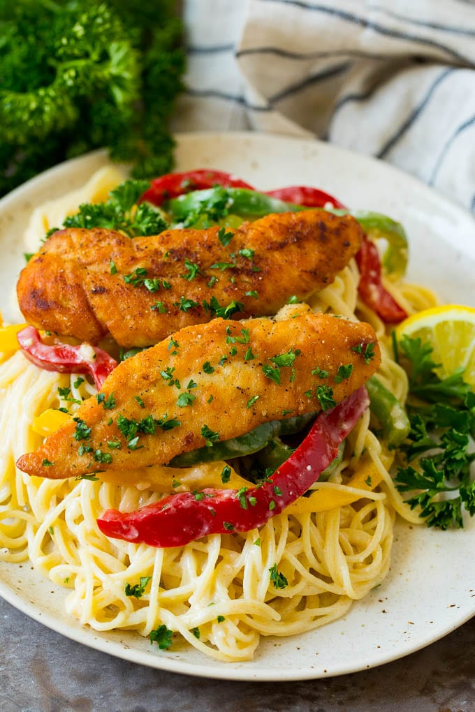 A plate of chicken scampi with angel hair pasta and red bell peppers.