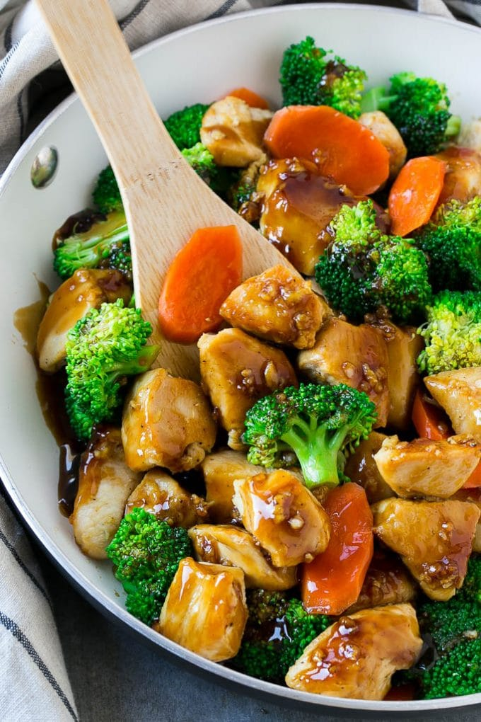 A pan of honey garlic chicken stir fry with a spatula in it.