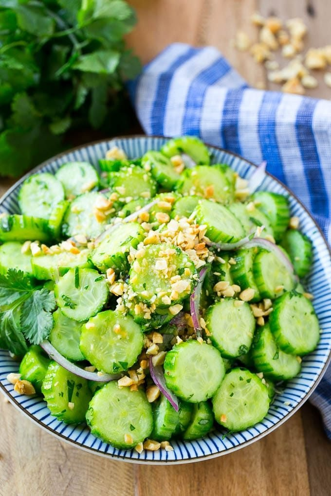 A bowl full of Thai cucumber salad that's topped with crushed peanuts and chopped cilantro.