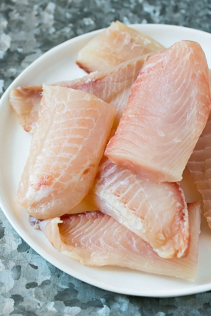 Tilapia fish fillets on a plate.