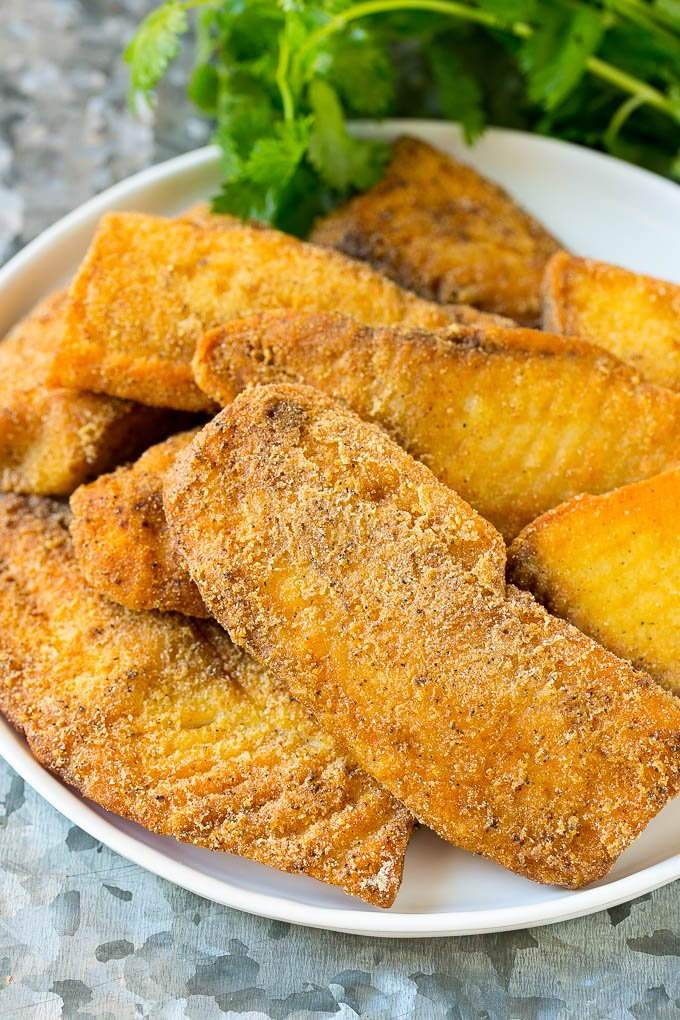 Fried and breaded fish fillets on a serving plate.