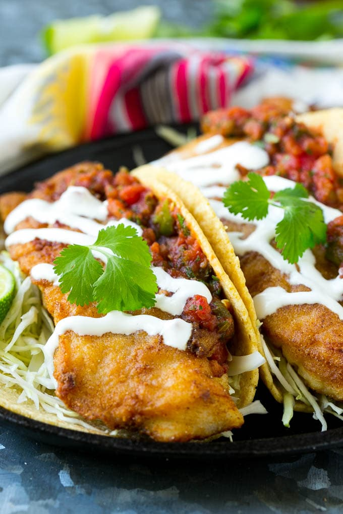 Baja fish tacos filled with fried fish, shredded cabbage, salsa and a creamy sauce.