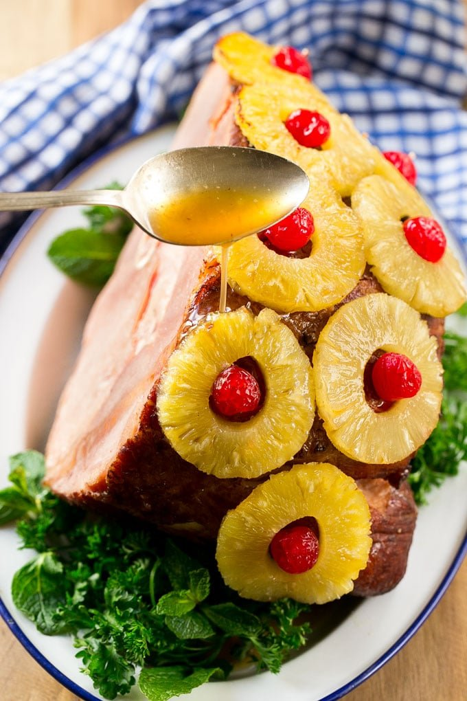 A spoon pouring glaze over a ham with pineapple and cherries.