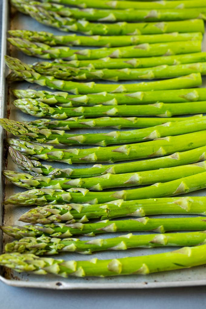 Fresh asparagus stalks on a sheet pan.