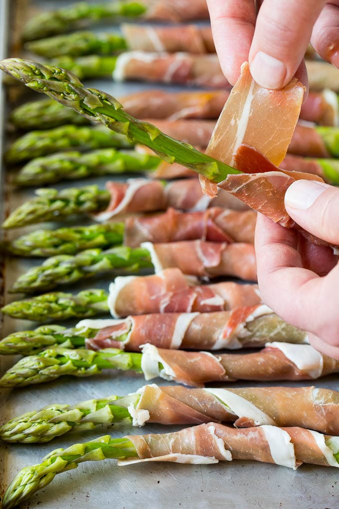 A hand wrapping a slice of prosciutto around an asparagus stalk.