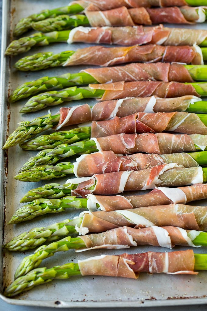Asparagus on a sheet pan with prosciutto, ready for the oven.