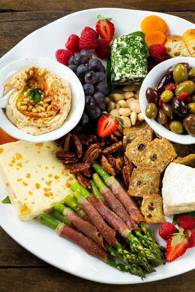 A platter with hummus, cheese, asparagus and nuts.