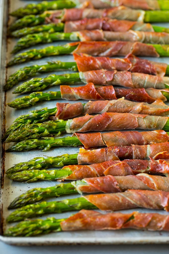 Prosciutto wrapped asparagus on a sheet pan.