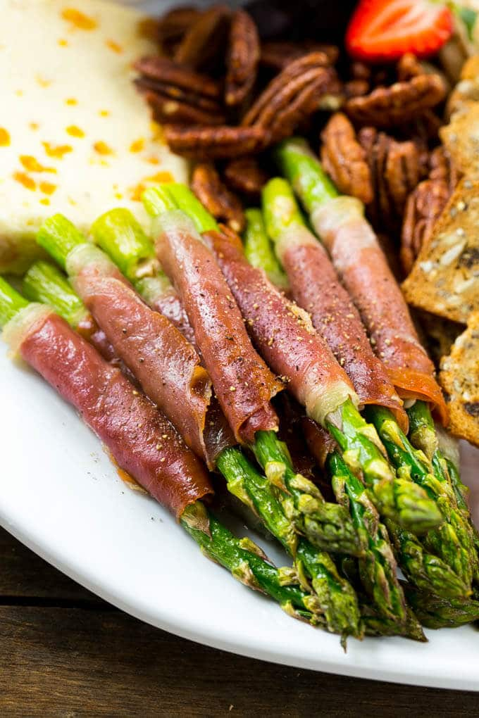 Prosciutto wrapped asparagus on a serving plate.
