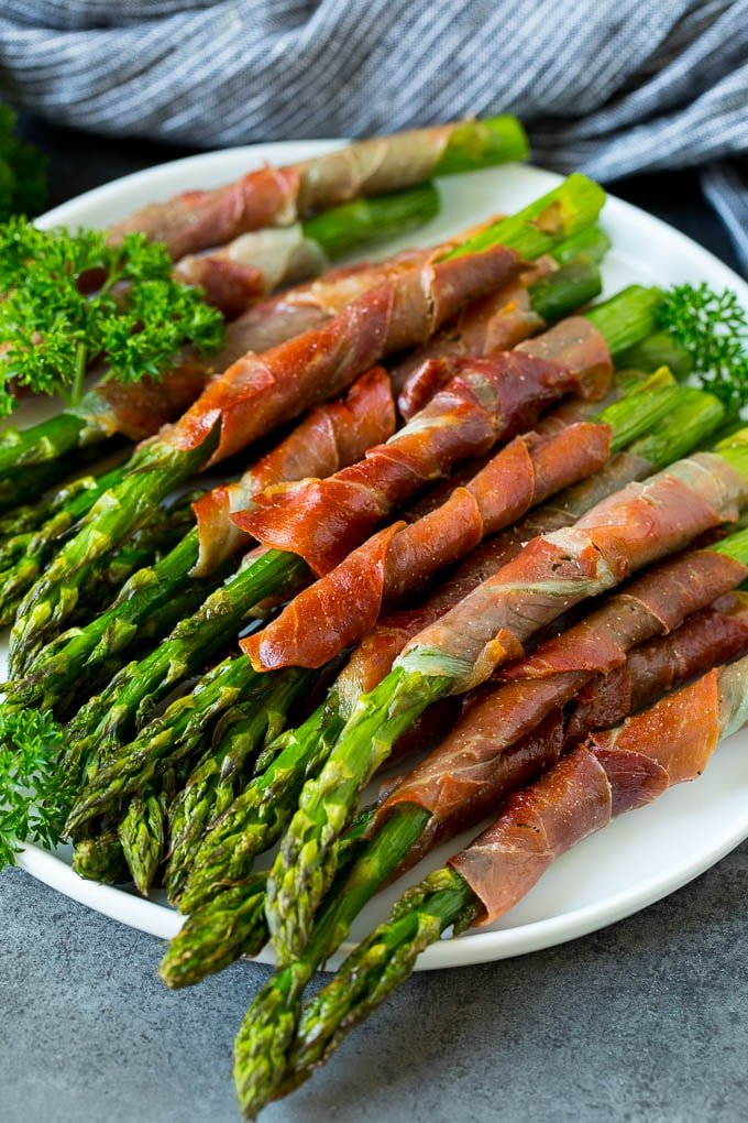 A plate of prosciutto wrapped asparagus garnished with fresh parsley.