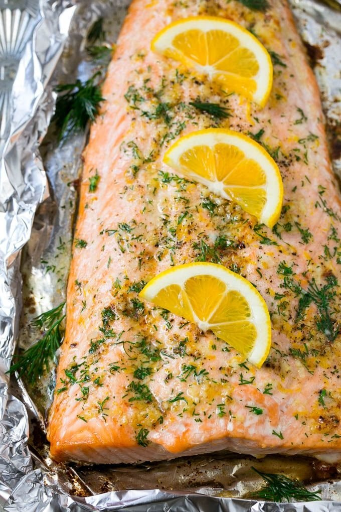 Salmon in foil in a garlic butter sauce with a topping of chopped fresh dill and lemon slices.