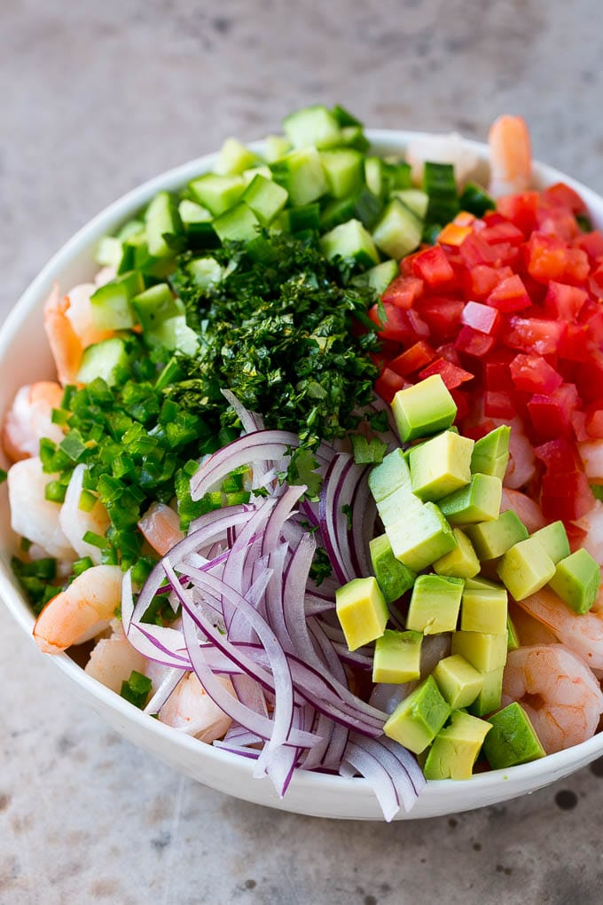Shrimp, avocado, red onion tomatoes, cilantro, jalapeno and cilantro in a bowl.