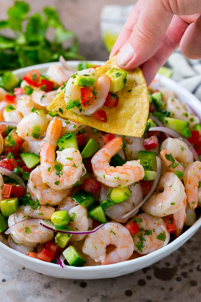 A bowl of shrimp ceviche with a tortilla chip scooping some out.
