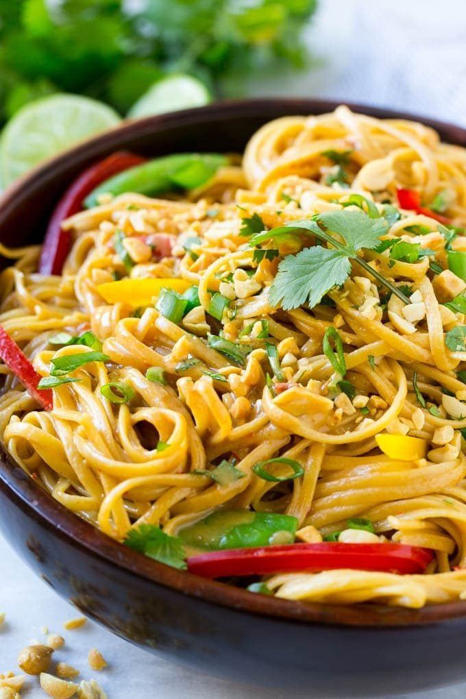 A bowl of Thai peanut noodles made with homemade peanut sauce, fresh vegetables and chopped peanuts.
