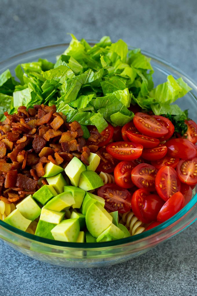 Bacon, lettuce, tomato, pasta and avocado in a bowl.