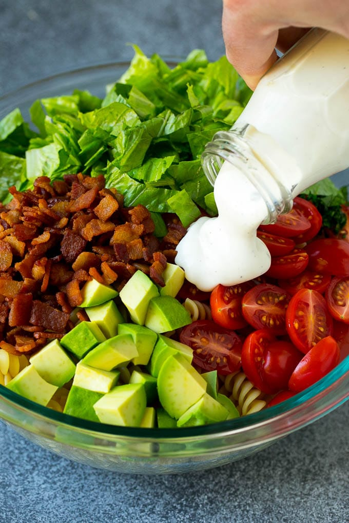 Ranch dressing being poured over tomatoes, lettuce, bacon and avocado.