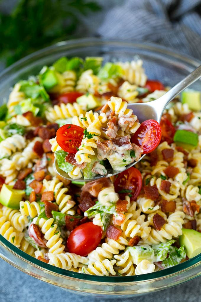 A serving spoon filled with BLT pasta salad.