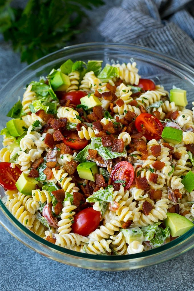 A bowl of BLT pasta salad with avocado in a creamy dressing.