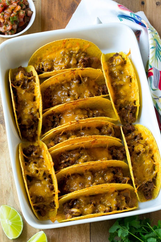 Baked beef tacos topped with melted cheese in a casserole dish.