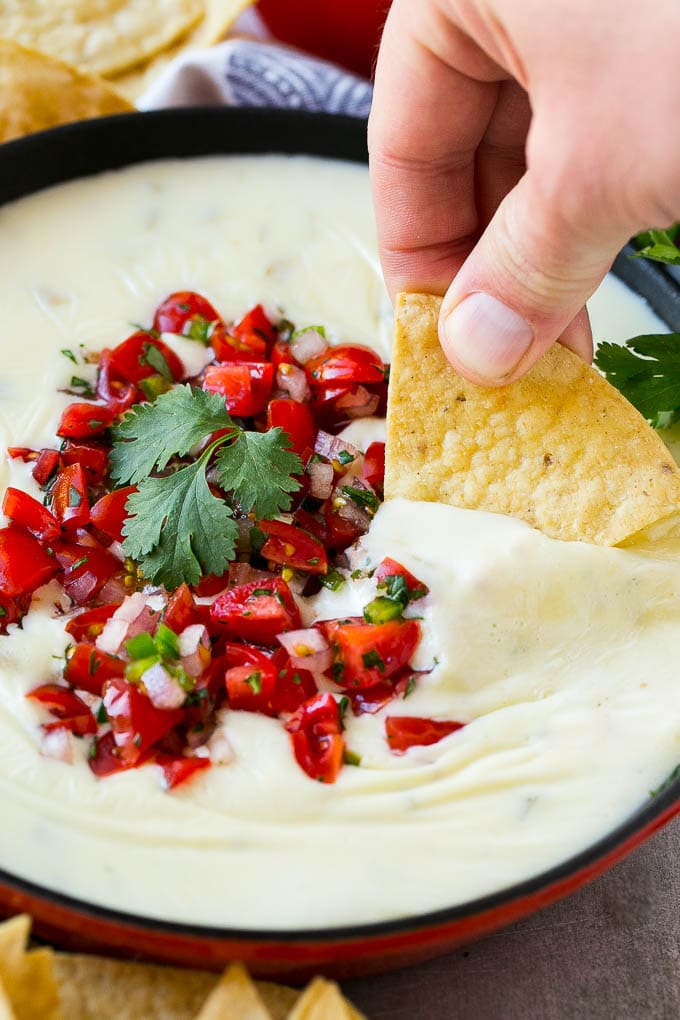 Restaurant style white queso dip skillet topped with fresh salsa.