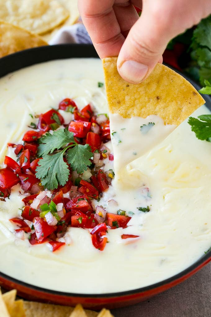 A pan of white queso dip topped with pico de gallo and served with tortilla chips.