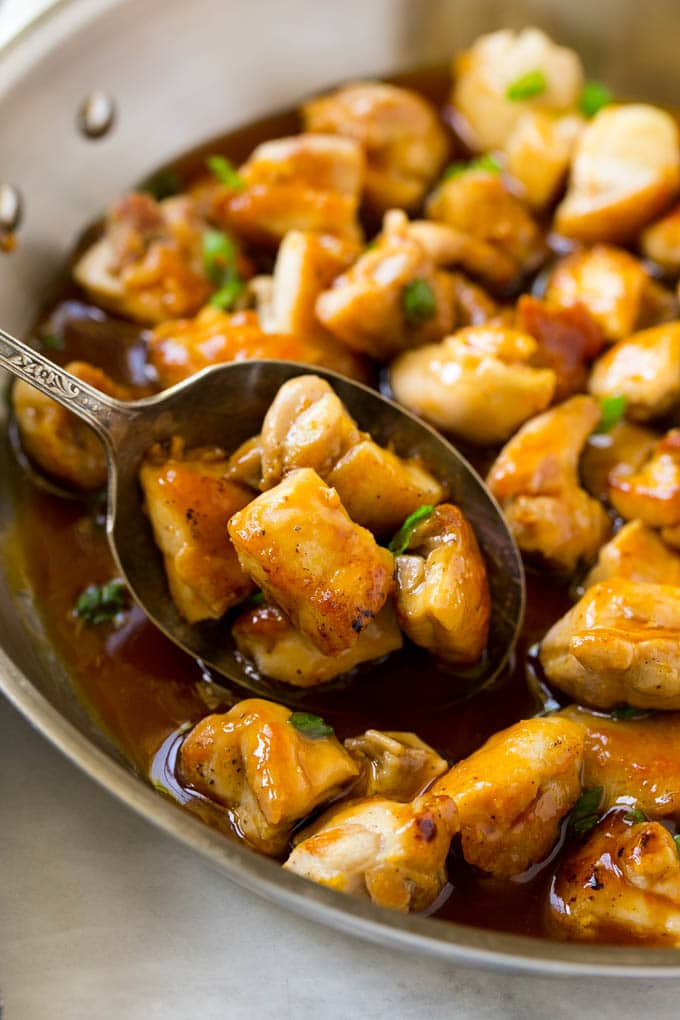 A pan of bourbon chicken with a serving spoon in it.