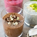 Three cups of chia pudding topped with chocolate and fruit, then garnished with mint.