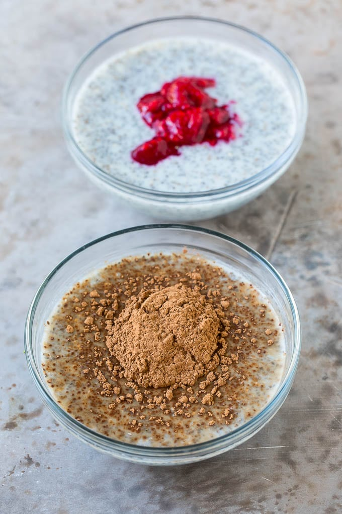 Bowls of chia pudding, one with cocoa powder on top and the other with crushed raspberries.