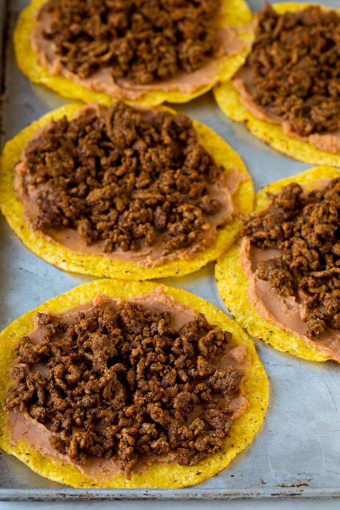 Tostada shells topped with refried beans and taco meat.