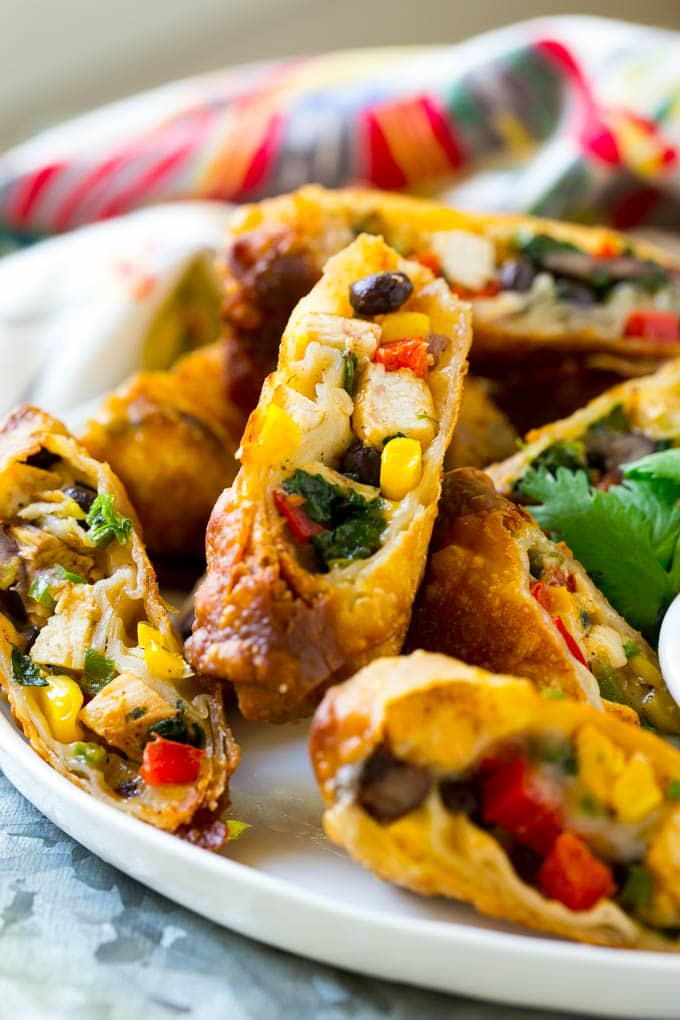Chicken egg rolls with colorful vegetables, cut and served with avocado ranch sauce.