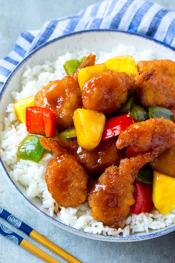A bowl of rice with sweet and sour shrimp, vegetables and pineapple chunks.