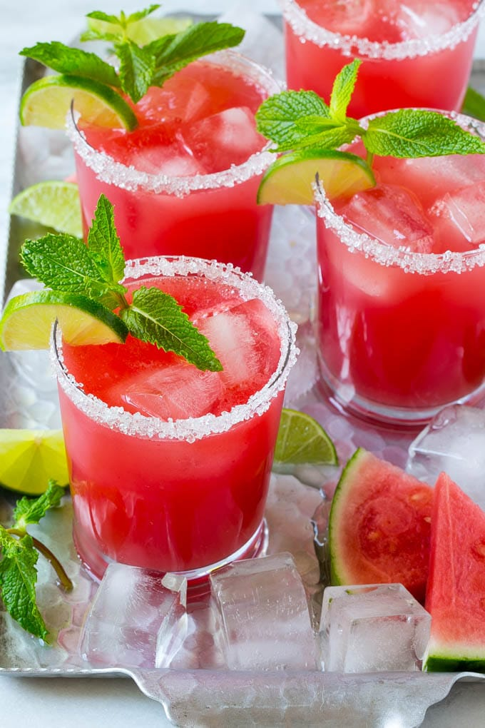 Watermelon agua fresca in sugar rimmed glasses with lime and mint for garnish.