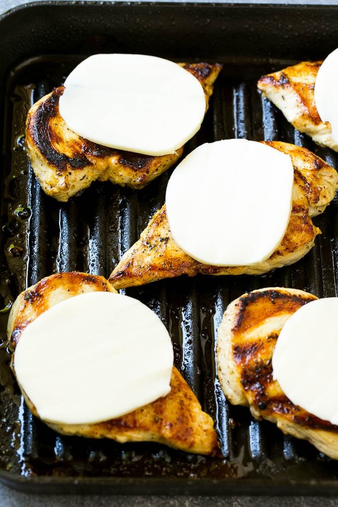 Grilled chicken with mozzarella cheese slices on top.