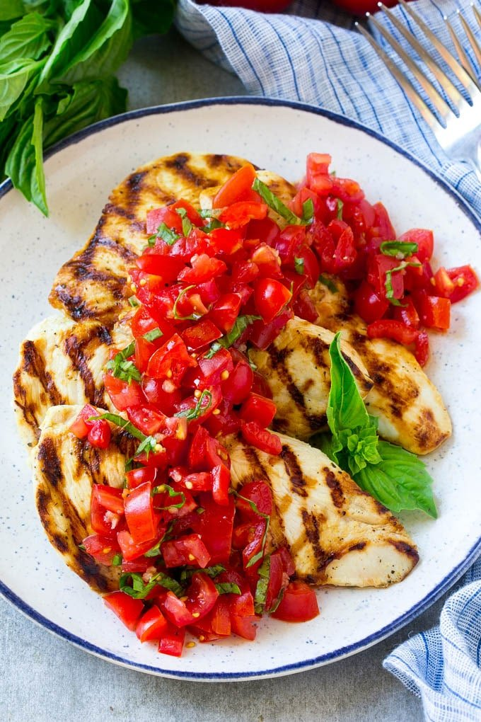 Chicken breasts on a white plate with blue rim, topped with chopped tomatoes and sliced basil.