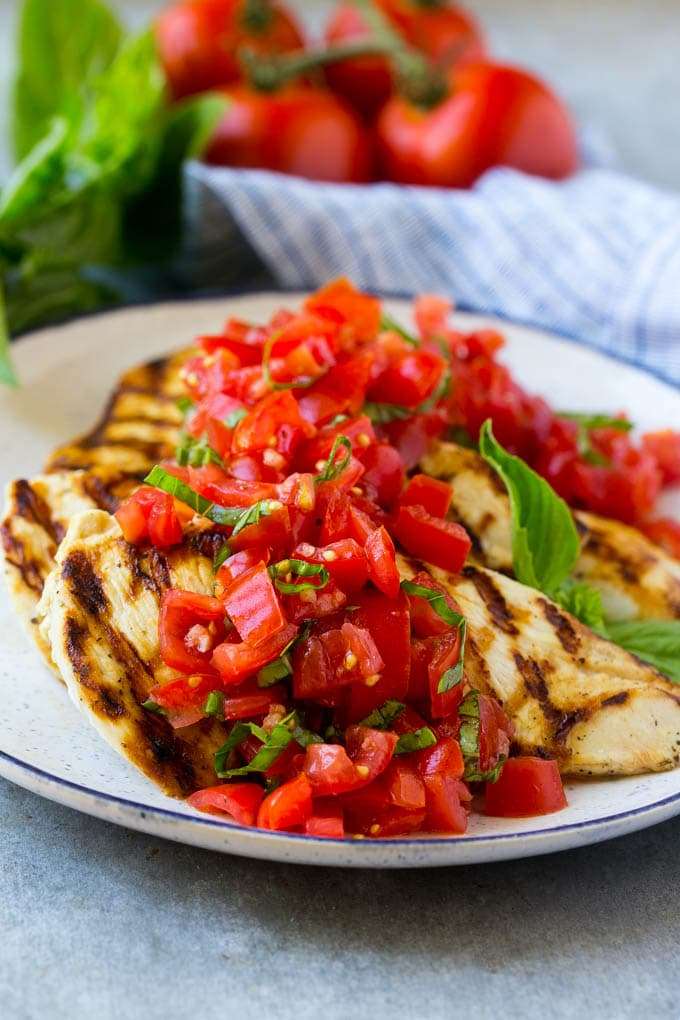 Chicken breasts that have been grilled, on a serving plate with tomatoes and basil on top.