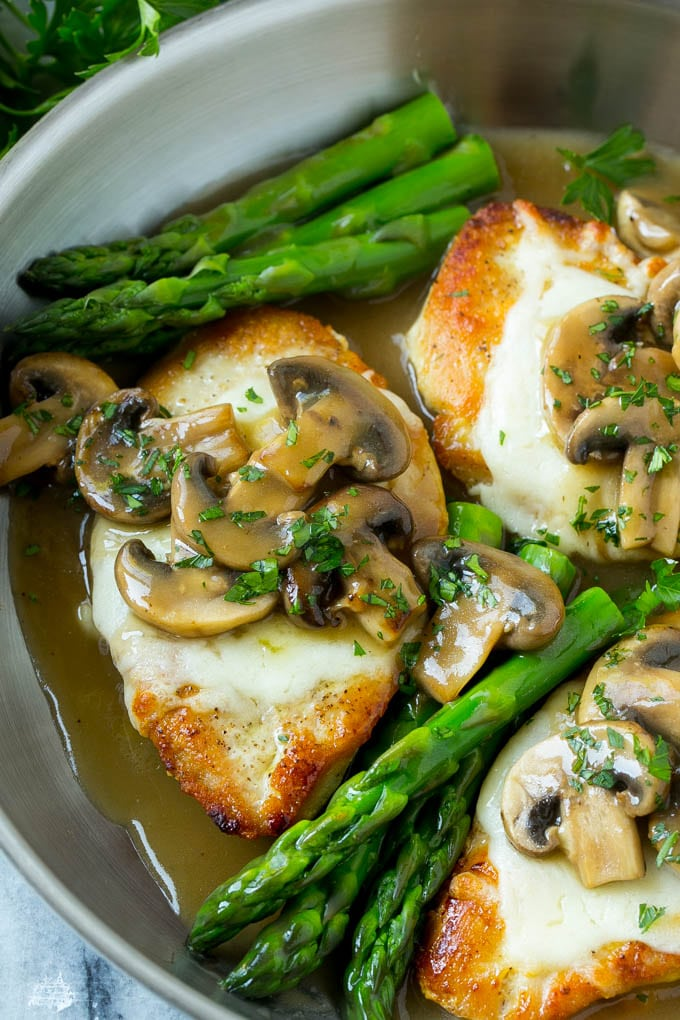 Golden brown chicken breasts topped with melted mozzarella cheese and mushroom sauce, in a pan with asparagus.
