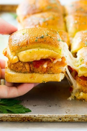 A crispy chicken sandwich being pulled away by a hand.