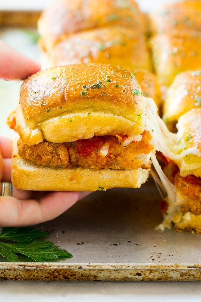 A crispy chicken parmesan slider being pulled away by a hand.