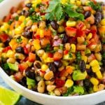 A bowl full of cowboy caviar made from finely diced vegetables, beans, black eyed peas and avocado.
