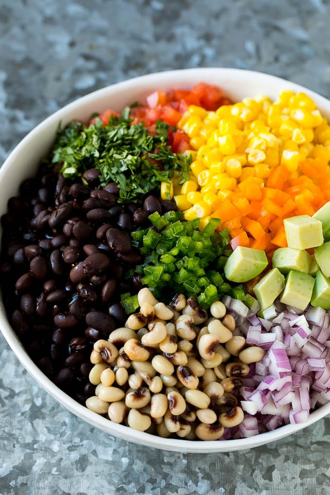 A bowl full of black beans, black eyed peas, tomatoes, corn, peppers and cilantro.