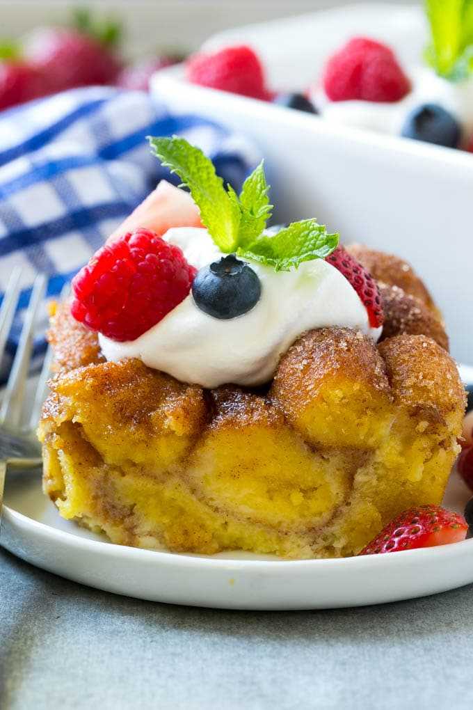 Slice of donut bread pudding topped with whipped cream and berries.