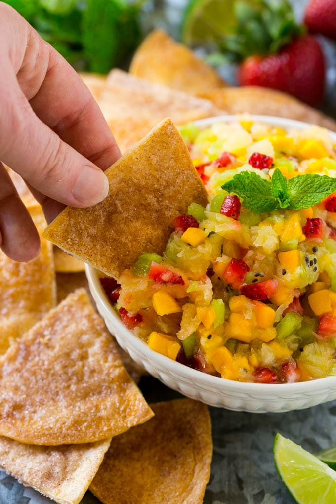 Diced fruit in a white bowl with a hand scooping out the fruit with a cinnamon sugar tortilla chip.